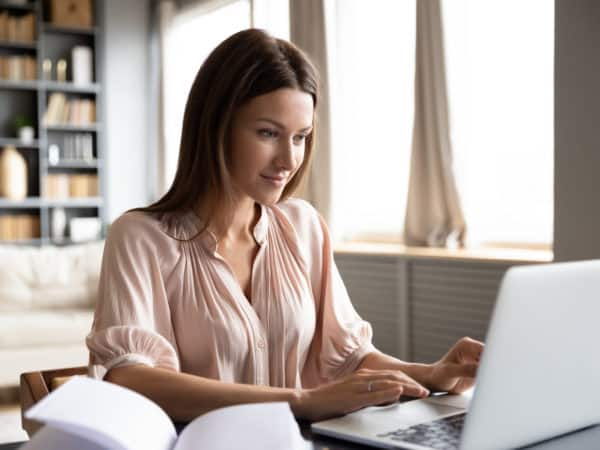 Pleasant happy young woman freelancer working on computer.